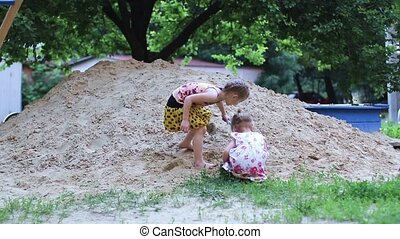 Childs playing sand in the sandbox - Two little girls sister...