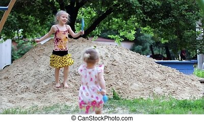 Two happy grils dancing in sandbox - Two little girls...
