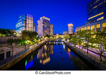 The Providence River and modern buildings at night, in...