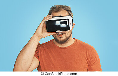 Young man wearing virtual reality goggles His livingroom...