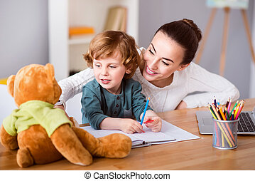 Mother and son looking at teddy bear