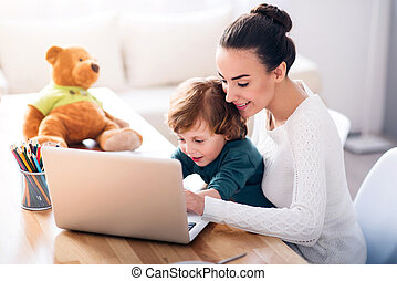 Mother and child using a laptop - Looking for cartoons Young...