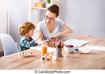 Woman painting with her son - Use this color. Smiling...