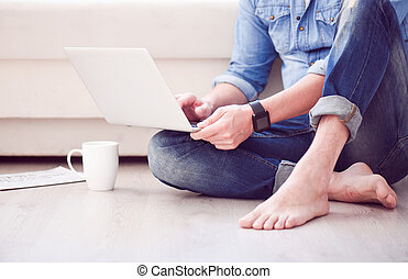Man sitting on floor and using laptop - Relaxed surfing in...
