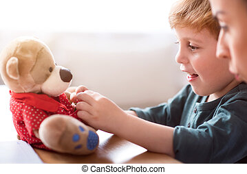 Little boy dressing teddy bear - Look at it. Amused little...