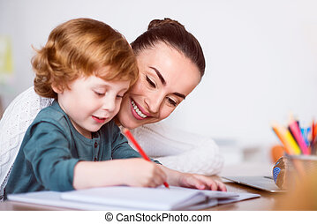 Mother teaching her son drawing