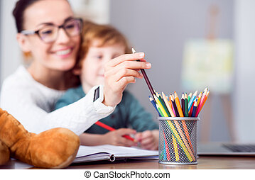 Woman taking a crayon from pencil cup - Source of...