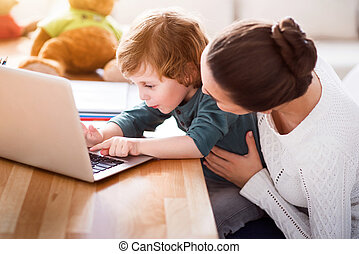 Mother teaching son using laptop - Little hacker. Mother...
