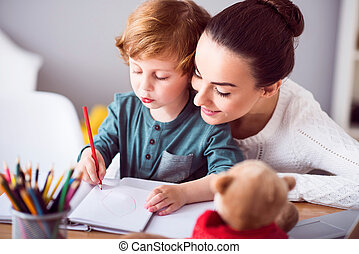 Mother looking at child drawing a picture