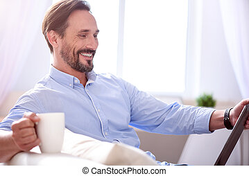 Man smiling and looking at the tablet