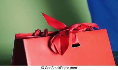 Hands in gloves untie a red ribbon of a luxury gift bag clip