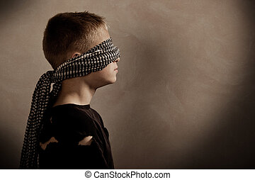 Serious boy blindfolded with copy space in front - Side...