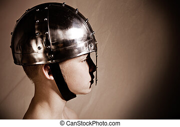 Side view of boy in warrior helmet with metal nose guard and...
