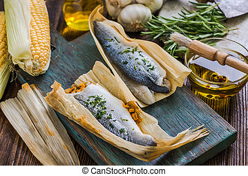 Seabass fish wrapped in corn husk, bbq preparation