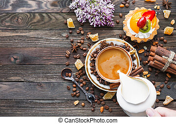 Rustic wooden background with cup of coffee, milk, fruit...
