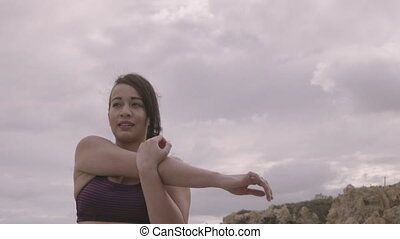 Young woman working out on the beach at cloudy weather. Stretching. Fitness. Slow Motion