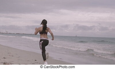 Young fit sports woman running on the beach. Super slow...