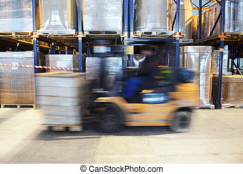 forklift in motion at warehouse - worker driving a forklift...
