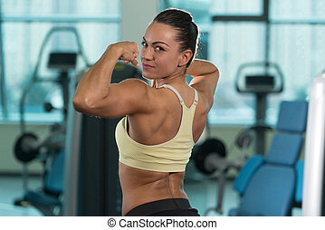 Healthy Young Woman Flexing Muscles - Portrait Of A Young...