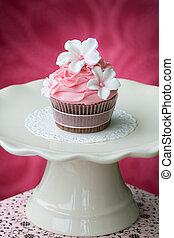 Pink cupcake on a cream colored cakestand