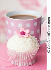 Cupcake decorated with dessicated coconut and a sugar flower