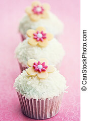 Cupcakes decorated with dessicated coconut and sugar flowers