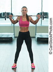 Woman Doing Heavy Weight Exercise With Barbell