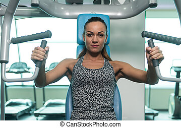 Young Sexy Fitness Woman Exercise Chest On Machine