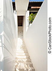 White stairs to the door of a modern mansion covered with...