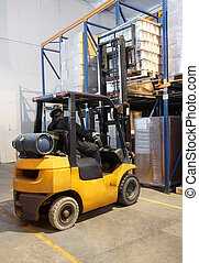 forklift loader stacking in warehouse - worker moving up the...