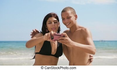 1-Teenagers Girl And Boy Taking Selfie With Phone On Beach -...