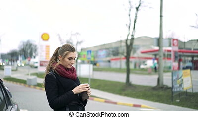 Beautiful girl drinks coffee at a gas station