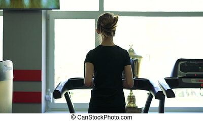Young healthy woman running on treadmill. 4k - Beautiful...