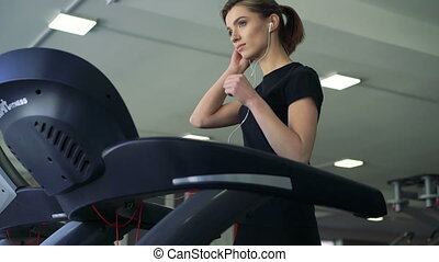 Close-up of a girl with headphones on a treadmill. 4k