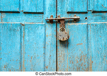 Padlock on a blue door - Padlock on a blue grungy door in...