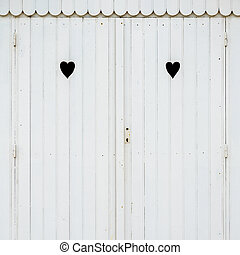 Two carved hearts on a white beach hut - Detail of white...