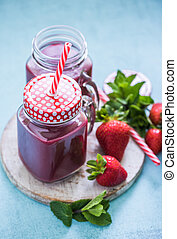 homemade strawberries smoothie in vitage jar with stripped...