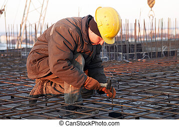 worker at construction site - worker in workwear making...