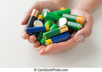 close up of hands holding alkaline batteries heap -...