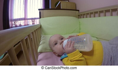baby holding and drinking milk from bottle himself. 4K -...