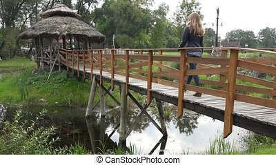 young woman walk on old wooden bridge in park at autumn. 4K