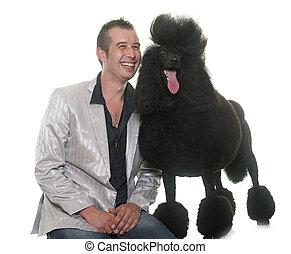 man and standard black poodle