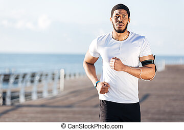 African young sportsman running on pier in the morning -...