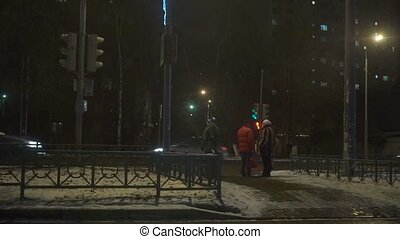 People crossing the busy street with traffic light. Winter...