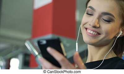 Young smiling woman at the gym listening to music using a...