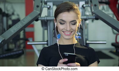 Close-up of a girl in the gym with a phone and a headset