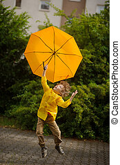 Little fellow flies over the yard with a yellow umbrella in hand