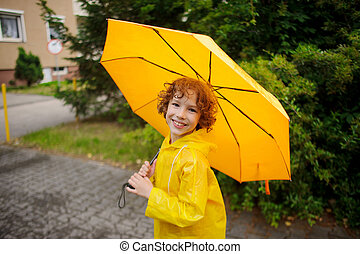 Cheerful boy of 8-9 years under a yellow umbrella The child...