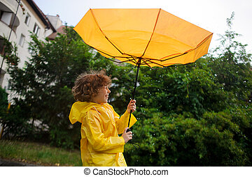 Strong wind has wrest an umbrella in boy and 39;s hands -...
