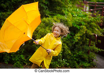 The boy in a bright yellow raincoat with effort holds an umbrella from wind.